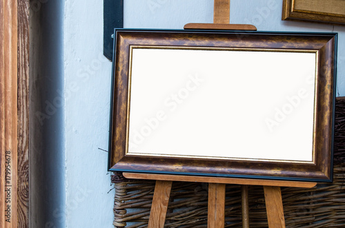 Ornate picture wooden frame on the easel in Art Gallery, Blank White Isolated Clipping Path