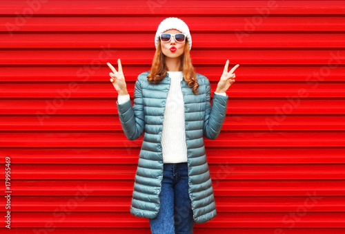 Fashion pretty woman blowing red lips doing air kiss posing on a background - 179955469