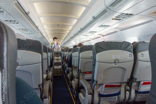 Stewardess offers food and drinks to economy class passengers on the plane