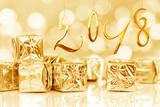 2018, small Christmas gifts in shiny golden paper, bokeh lights background - 179969264
