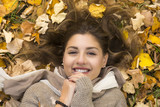 Smiling sweet girl lies down over autumn leaves - 179970431