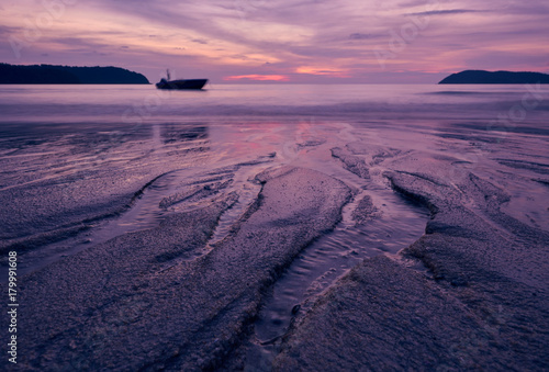 Fotobehang Zee zonsondergang Sunset over Pantai Cenang beach with pink colours, blur background and silhouette of boat. Langkawi, Malaisiya.