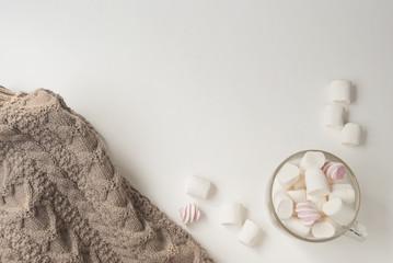 Warm cozy sweater and marshmallow. Winter concept. Flat lay. Top view © kozhevnikofa