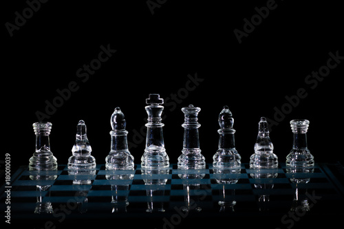 Plakat Glass Chess Set Standing on a Chessboard with a Dark Background, including the R