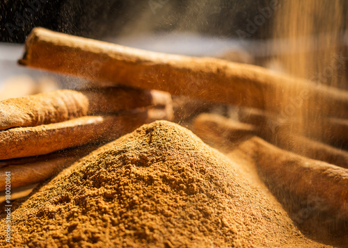 Fridge magnet Cinnamon sticks and powder close up on wooden table