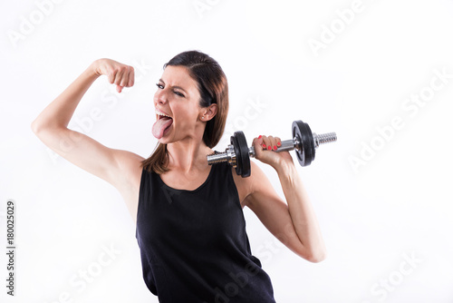Wall mural Young woman showing muscles