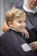 Happy boy at hairdresser's.