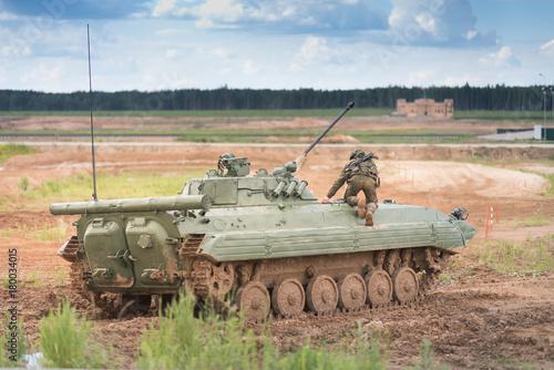 Combat Vehicle of the Airborne na poligonie w pobliżu Moskwy. Zbiornik na polu z niebieskim niebem i ciężkimi chmurami. żołnierz w pełnej amunicji na zbroi. Wspina się wewnątrz maszyny