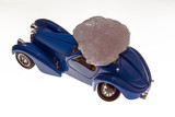 A natural stone on top of a model antique car