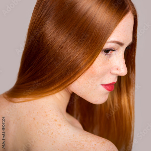 Foto op Canvas Kapsalon Portrait of a beautiful young woman with long red hair. Close-up photo in profile