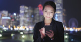 Business woman use of cellphone at night