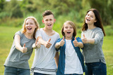 Happy girls and boys posing with thumbs up - 180074871