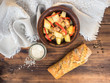 Baked meat with potatoes, bread, salt and spices on the background of wooden table and coarse cloth. Roast potatoes in a clay bowl with a wooden spoon. Rural still life. The top view.
