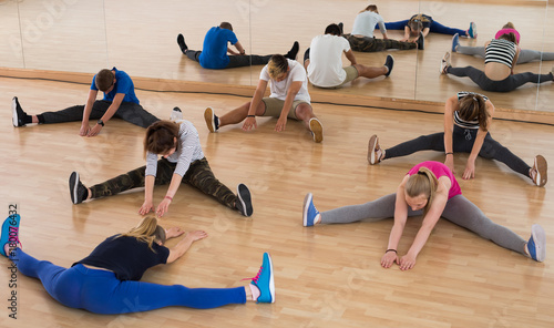 Poster Teenage boys and girls with trainer stretching in dance hall