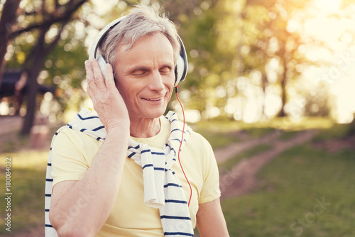 Foto op Canvas Amusementspark Favourite music. Delighted positive aged man wearing headphones and listening to music while walking in the forest