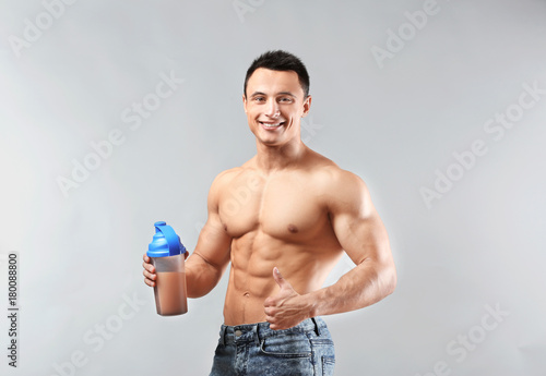 Sporty young man with protein shake on light background