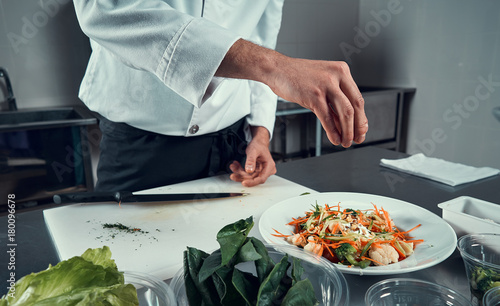 Fridge magnet The chef prepares the dish. Sprinkle the salad with spices. Cooking. Professional kitchen. Salad dressing. Spices for salad