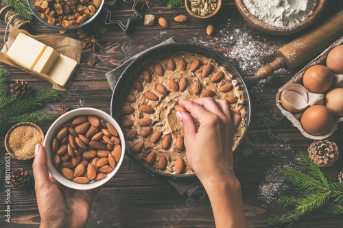 Cooking christmas pastry. Young woman's hands decorating festive fruit cake with almond. Wooden table with baking ingredients