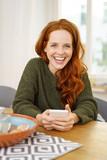 lachende frau sitzt zuhause am tisch mit ihrem handy - 180108858