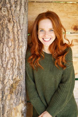 glückliche frau mit langen roten haaren lehnt an einem baumstamm - 180109494