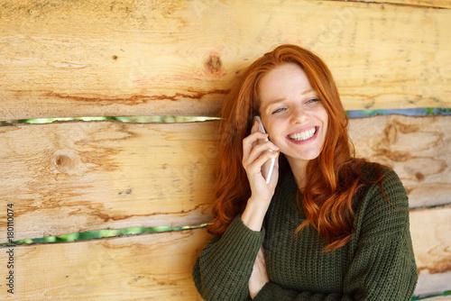 frau steht lächelnd draußen an einer holzwand und telefoniert - 180110074