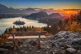 Fototapety Bled, Slovenia - Beautiful panormaic skyline autumn view with hilltop bench and colorful sunrise of Lake Bled and Pilgrimage Church of the Assumption of Maria
