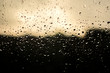 Abstract shot of rain drops on the window of a car with sunset colors.