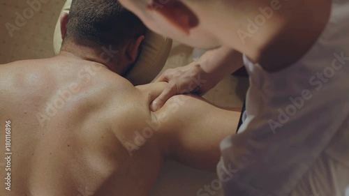 Tuinposter Gymnastiek Top view of masseur makes a male back massage in spa center 4K