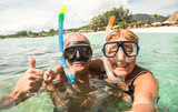 Senior happy couple taking selfie in tropical sea excursion with water camera - Boat trip snorkeling in exotic scenarios - Active retired elderly and fun concept around the world - Warm bright filter - 180120878