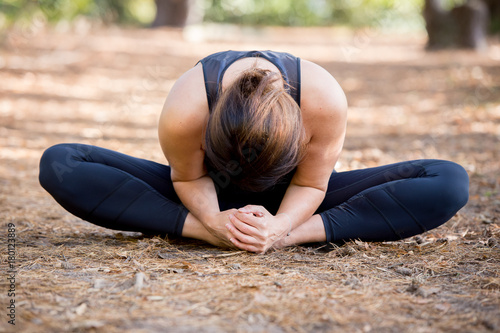 Fotobehang School de yoga Woman practicing yoga in the sand - Bound Angle Pose Forward - Baddha Konasana - Autumn day
