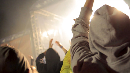 Back view of crowd of people at the concert. Footage. Silhouettes of concert crowd in front of bright stage lights. Cheering crowd at a rock concert