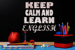 Motivation text Keep calm and learn English on school black chalkboard with school accessories