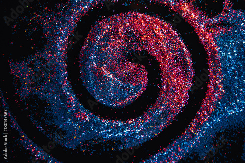 Fototapeta Colorful glitter swirl background. Milky way galaxy on contrast black background concept