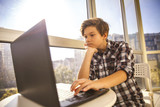 Teen boy using laptop by window - 180142679
