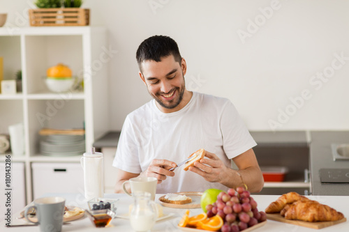 man eating toast with coffee at home kitchen