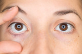 Close up view of young woman opening with fingers her right eye