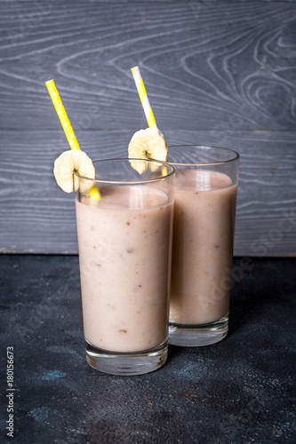 Foto op Aluminium Milkshake Banana and milk smoothie in glasses on gray background
