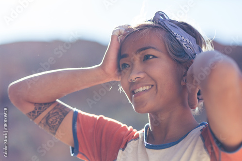 Young asian woman outdoors smiles while watching friends rock climbing in the de Poster