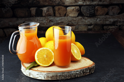 Fotobehang Sap glass jar of fresh orange juice with fresh fruits on dark table