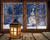 Laterne vor einem Fenster mit Blick auf verschneiten Winterwald und Weihnachtsbaum - 180166877