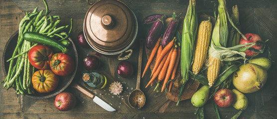 Fall cooking background. Autumn ingredients for Thanksgiving day dinner preparation. Flat-lay of green beans, corn cobs, carrot, tomatoes, eggplant, fruits over wooden table, top view