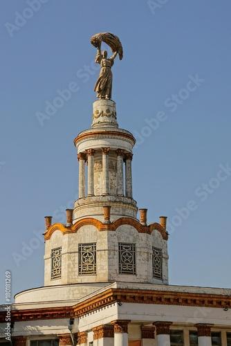 Foto op Plexiglas Kiev верхушка исторического здания с фигурой женщины на фоне неба
