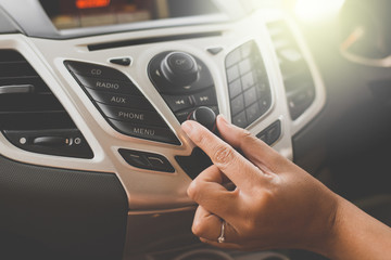 Hand turning on car radio system,Button on dashboard in car panel