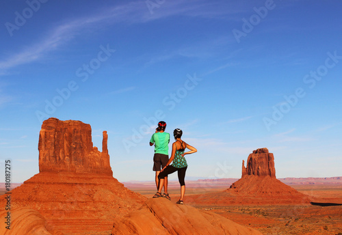 Foto op Canvas Baksteen Couple Hiking Monument Valley with The Mittens