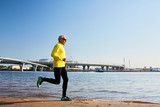 Mature runner working out along river bank with cityscape on background