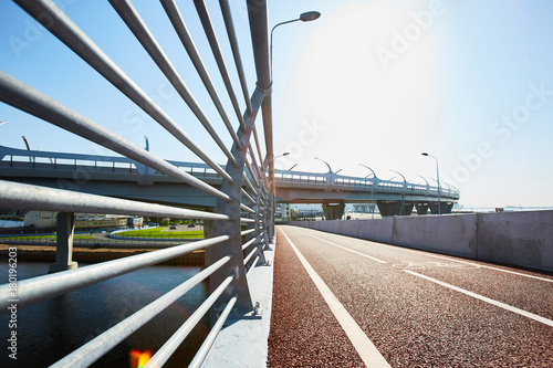 Race track of modern stadium and bridge railings over waterside