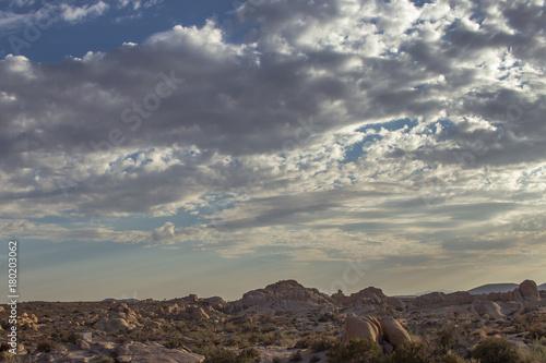 Fotobehang Donkergrijs Rocky Cloudy Desert Landscape Sunset