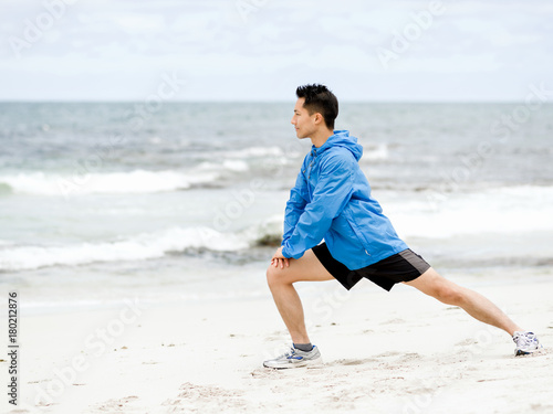Poster Young man doing exercise at the beach