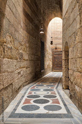 Poster Smal steegje Arched corridor leading to the courtyard of Sultan Barquq mosque with stone bricks wall, ornate colored marble floor and wooden door, Old Cairo, Egypt