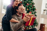 Young couple having fun celebrating Christmas with gifts. - 180223070